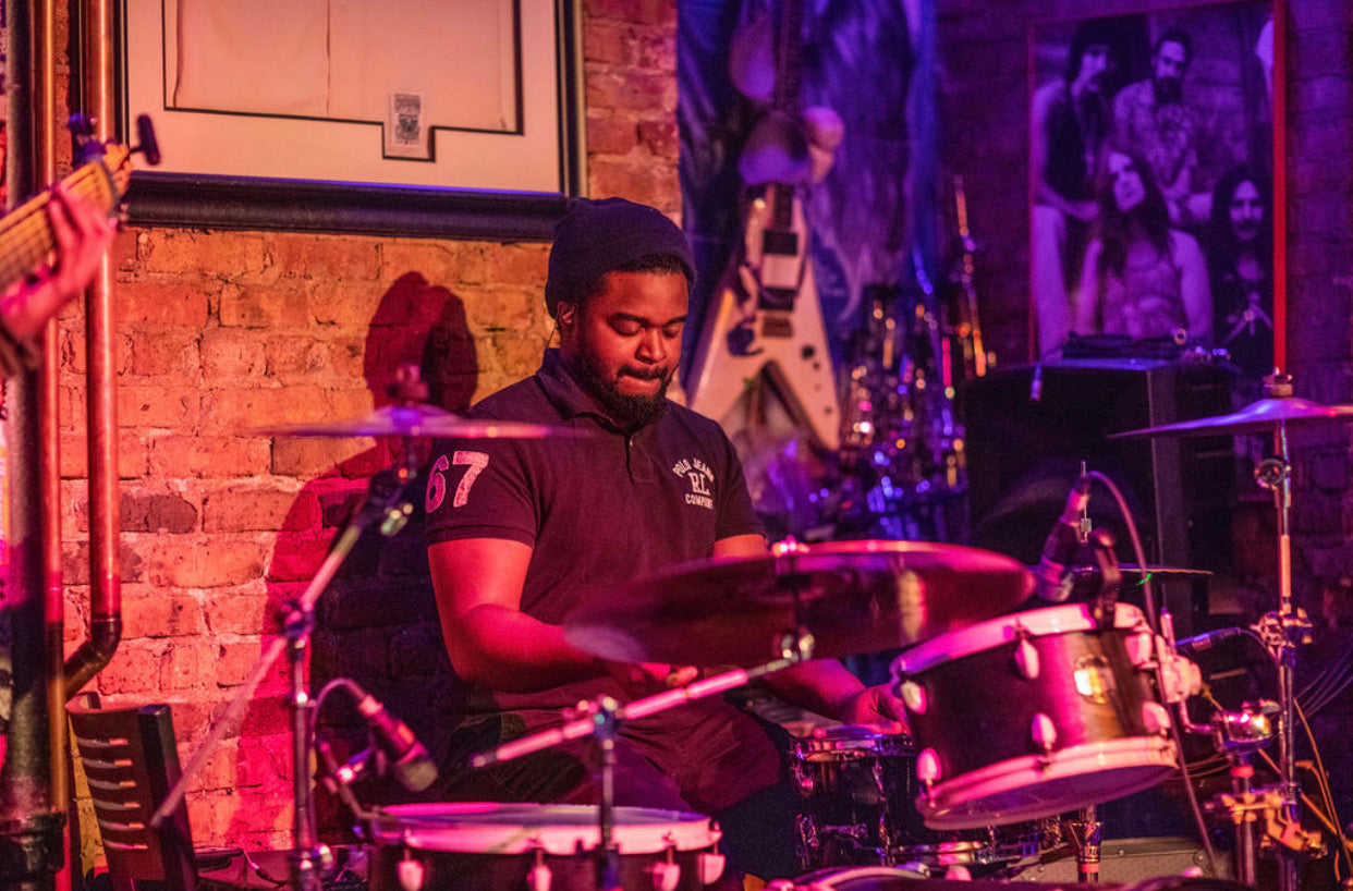 Drummer Corey Willaby poses with Scorpion Percussion drumsticks behind his drumkit