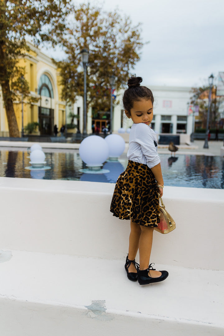 Girl by fountain wearing leopard skirt