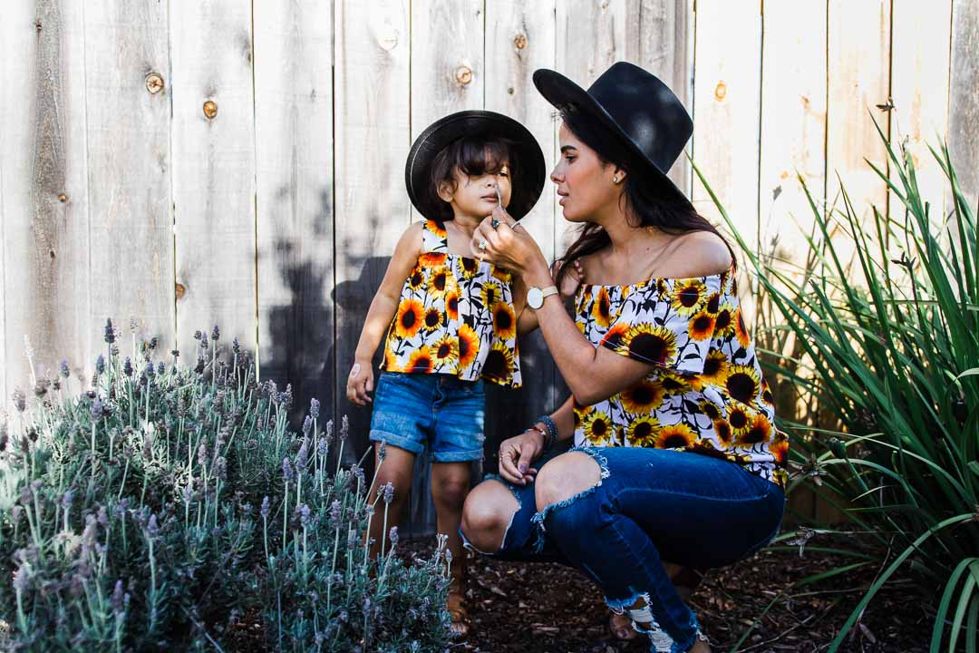 mom and daughter wearing sunflower matching tops and jeans