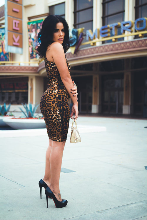 Woman by theater wearing leopard Dress