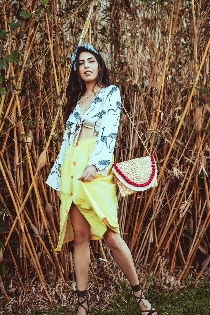 button front yellow midi skirt worn by woman next to bamboo trees