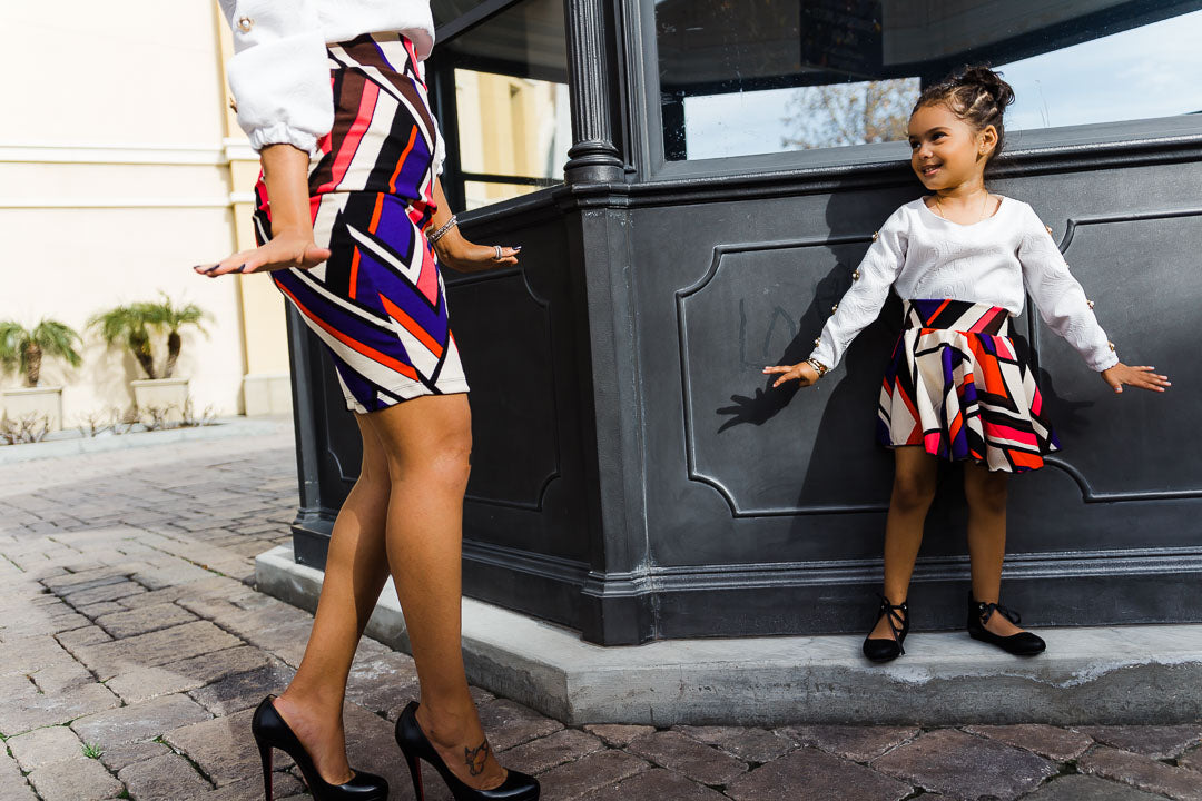girl against wall wearing colorful chevron skirt