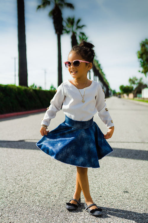 girl modeling blue circle skirt and white top