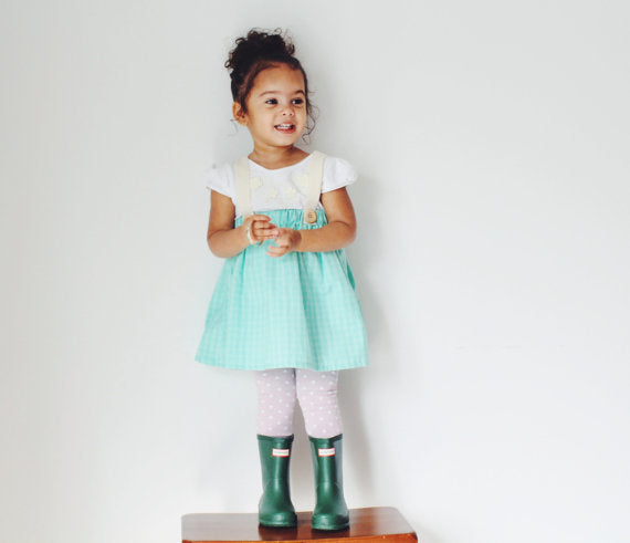little girl wearing  a light blue suspender skirt, green boots and white top