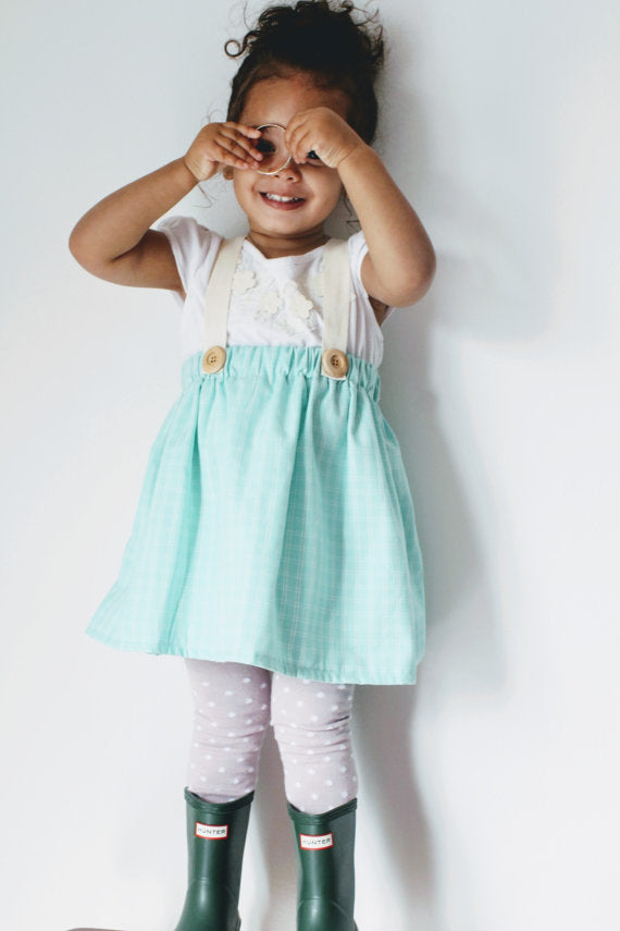 toddler girl covering eyes while wearing blue skirt