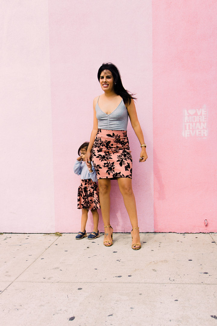 mom and daughter wearing matching beige and black skirts by pink wall