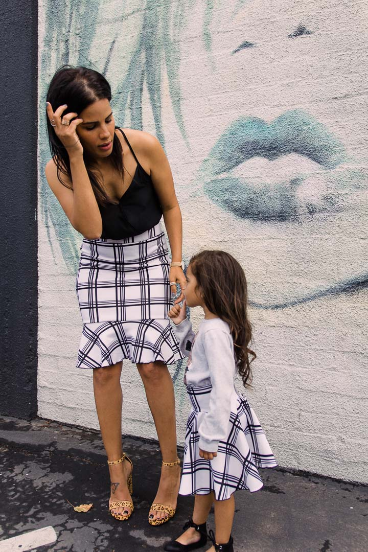 mother and daughter posing with matching skirt outfits