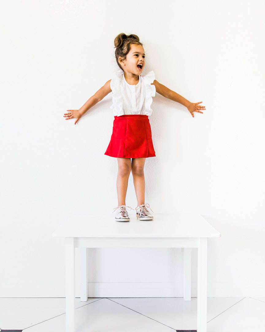 Little girl wearing a white top and red skirt