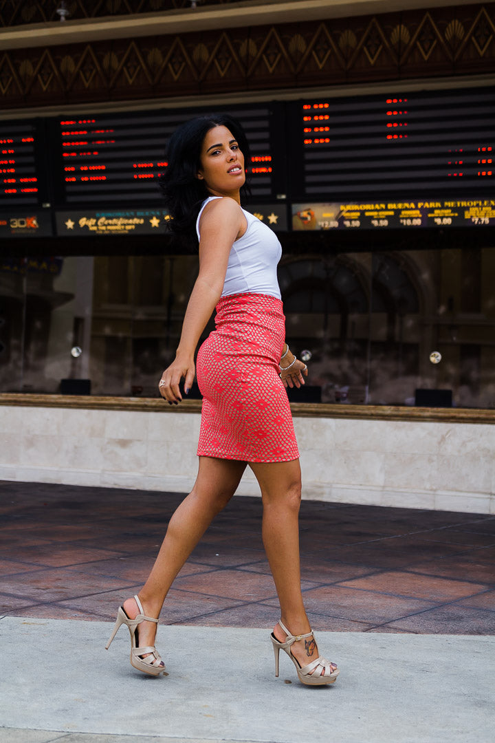 woman walking, wearing coral skirt and white top