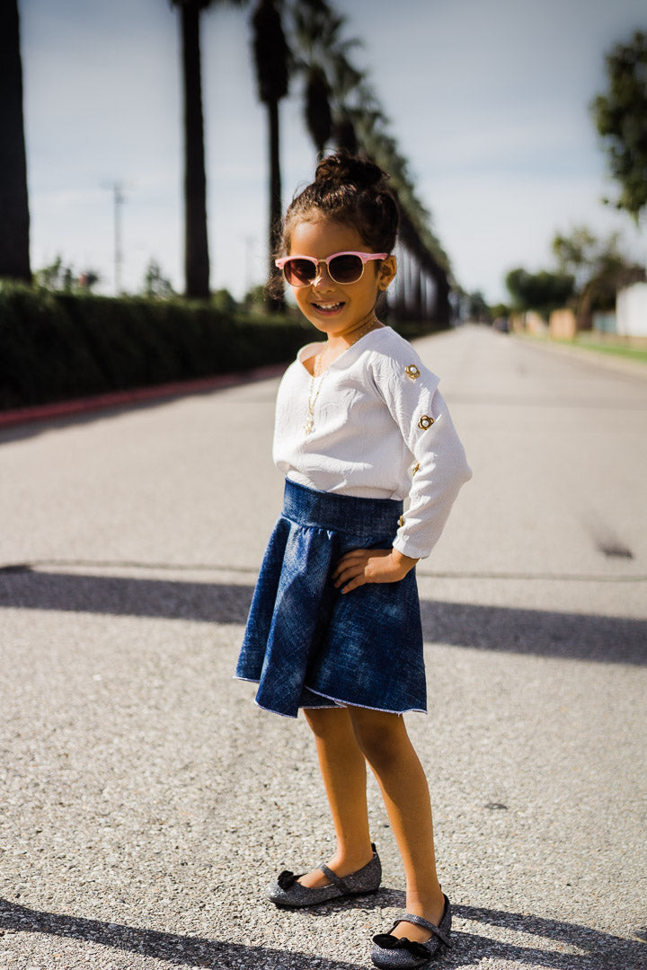 young girl wearing denim skirt and white top