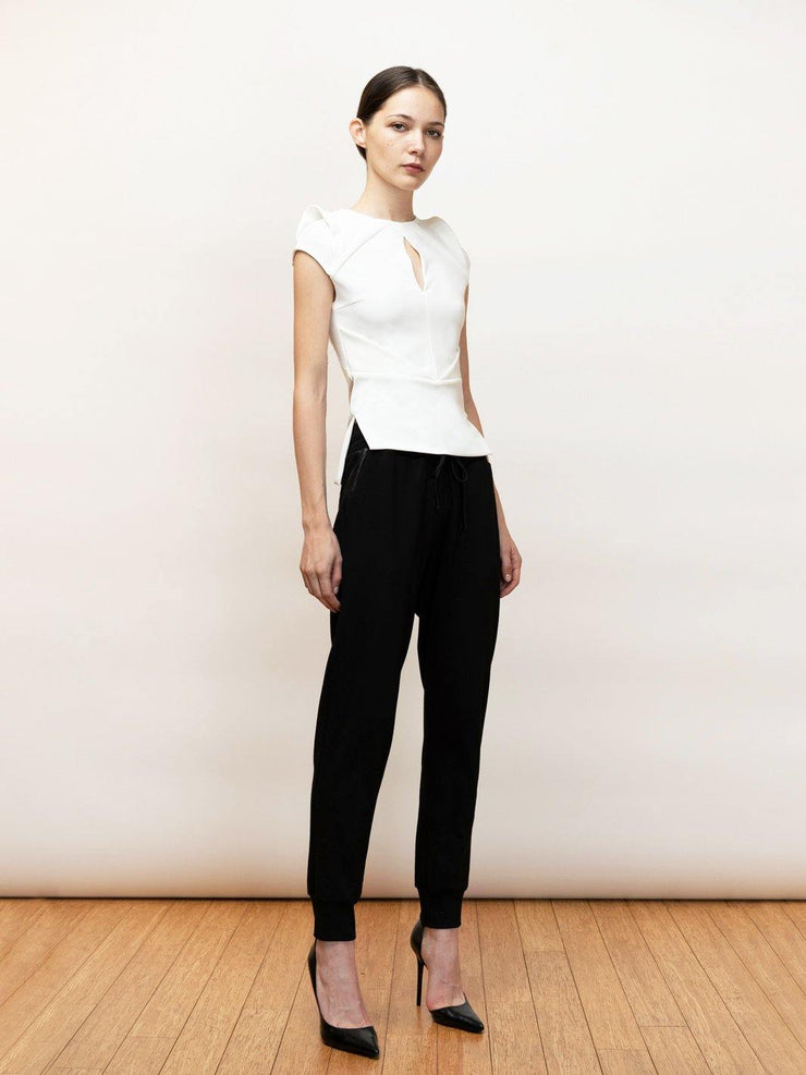 Tesee sleeveless stretch top with draping detail.