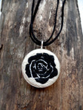 bold graphic black rose is set against a soft white background