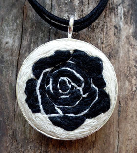 "handmade embroidered pendant. Includes a 43mm silver bezel hung by a 34"" double suede cord"