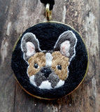 hand embroidered and set in gold bezel