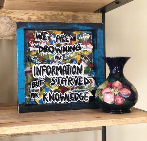 "wooden box painted blue and black with brightly colored paper scraps and the words, ""we are drowning in information but starved for knowledge."""
