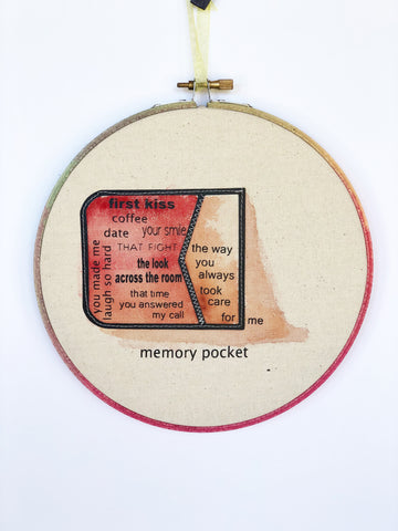 a round wooden painted hoop with canvas, a painted red pocket on its side with the words spilling out...memory pocket, first kiss, coffee date, your smile, the look across the room, that time you answered my call, you always made me laugh so har, the way you always took care for me.