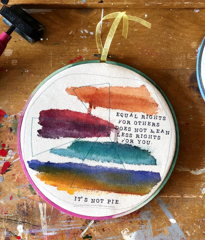 "a round multicolored wooden hoop with the words, ""equal rights for others does not mean less rights for you.. it's not pie."""