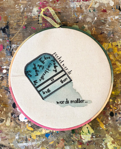 "a canvas hoop art piece with a blue painted upside down pocket and the words, ""you, me life together love fake, hate, privilege, can't breathe, truth, us, them and words matter.."""