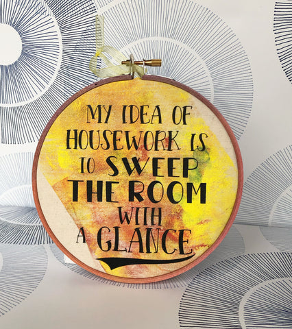 "round wooden hoop with yellow-orange paint and the words, ""My idea of housework is to sweep the room with a glance."""