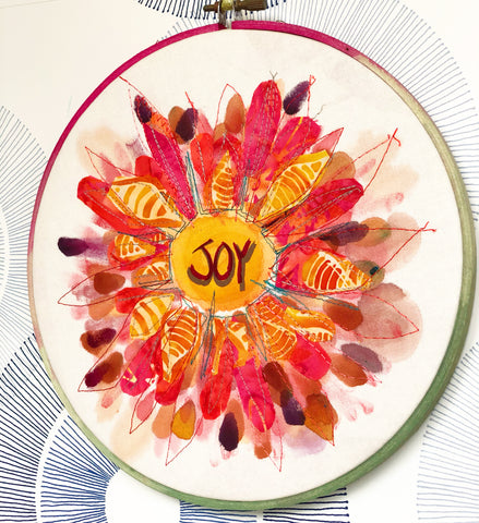 ound wooden hoop with fabric pieces and paint, and the word 'Joy' in the middle