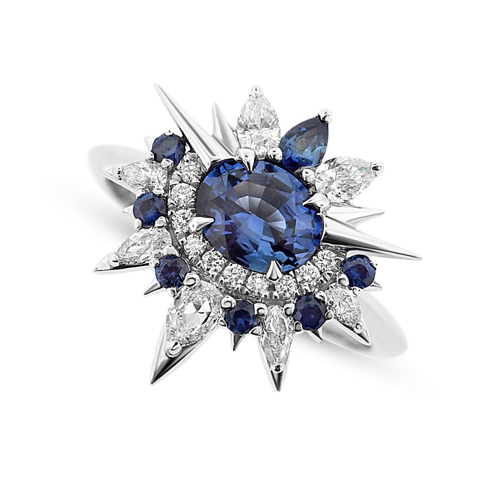 Bespoke fine jewelry multi-point star ring with blue sapphires, diamonds, and a thin round white gold band. The central setting is a round blue sapphire topped with pear- shaped blue sapphires and diamonds. On either side of these, 1 small white gold poi