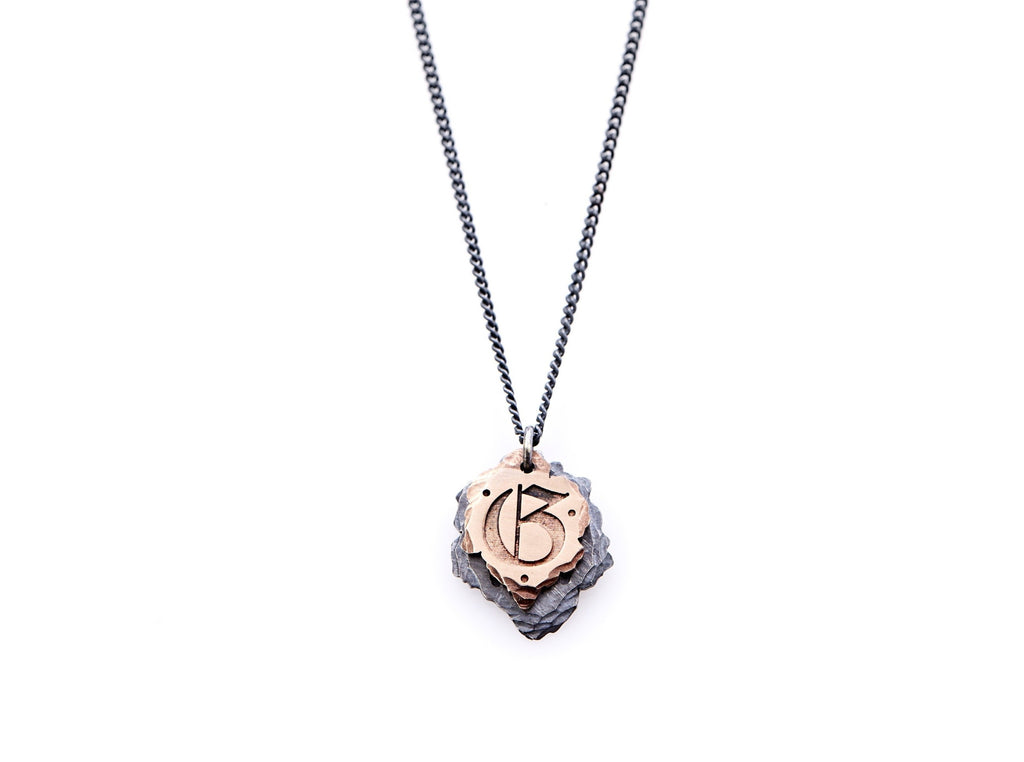 "Hand crafted, customizable Initial Necklace with 2 jagged-edged plates hanging from an oxidized sterling silver curbed chain. Top plate is hand forged rose gold with a custom engraving of the letter ""G"" in Old English lettering with 2 hand engraved dots on either side. Bottom plate is hand forged oxidized sterling silver and slightly larger than the rose gold plate. The top plate partially covers the bottom plate, and edges of cross- bones are visible on the bottom plate."