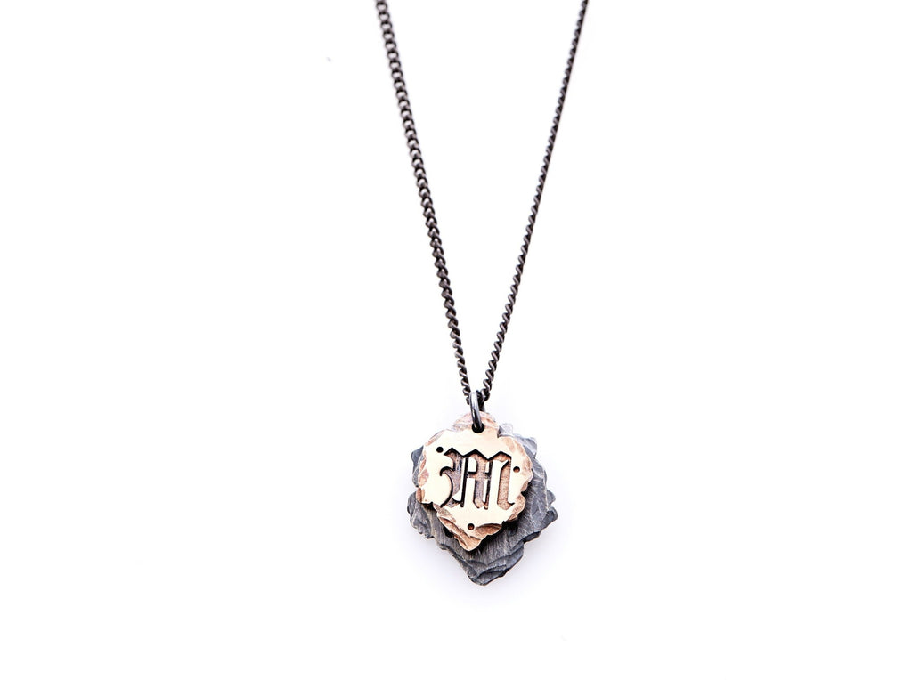 "Hand crafted, customizable Initial Necklace with 2 jagged-edged plates hanging from an oxidized sterling silver curbed chain. Top plate is hand forged rose gold with a custom engraving of the letter ""M"" in Old English lettering with 2 hand engraved dots on either side. Bottom plate is hand forged oxidized sterling silver and slightly larger than the rose gold plate. The top plate partially covers the bottom plate, and edges of cross- bones are visible on the bottom plate."