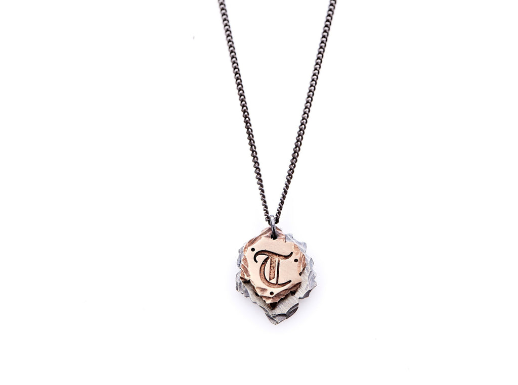 "Hand crafted, customizable Initial Necklace with 2 jagged-edged plates hanging from an oxidized sterling silver curbed chain. Top plate is hand forged rose gold with a custom engraving of the letter ""T"" in Old English lettering with 2 hand engraved dots on either side. Bottom plate is hand forged oxidized sterling silver and slightly larger than the rose gold plate. The top plate partially covers the bottom plate, and edges of cross- bones are visible on the bottom plate."