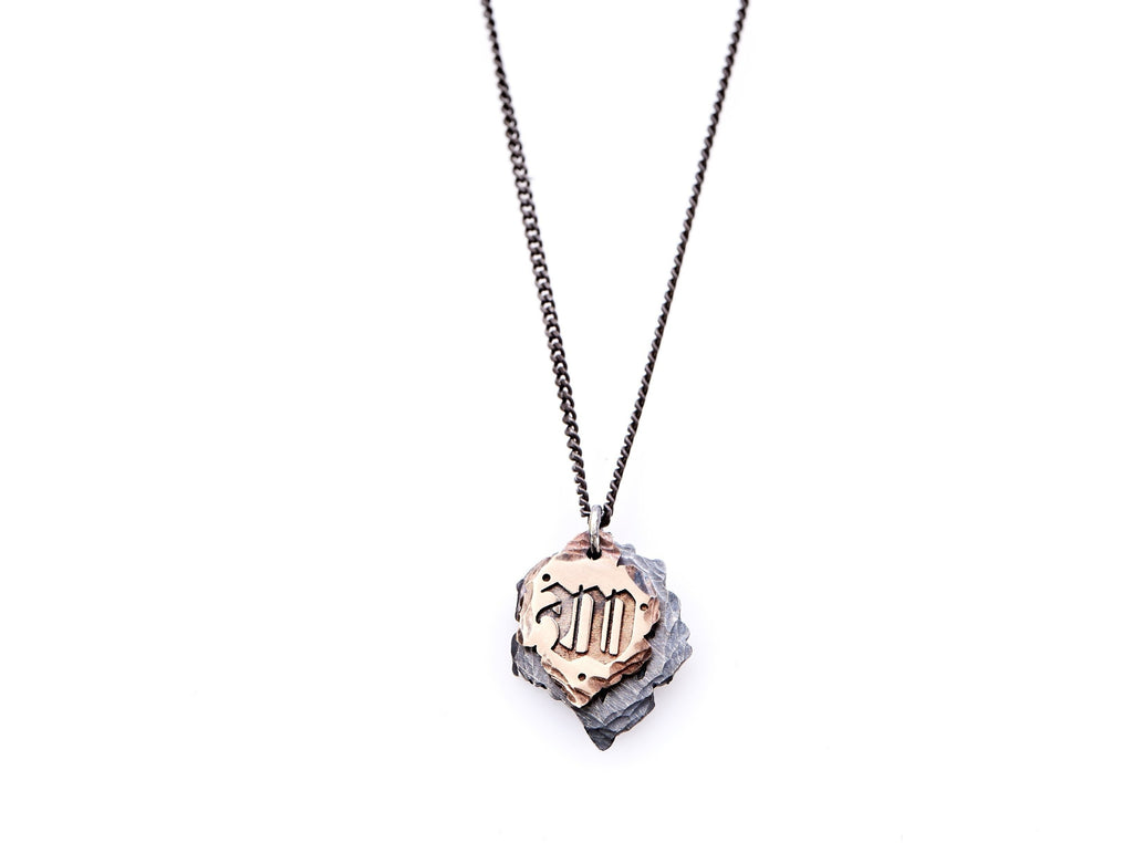 "Hand crafted, customizable Initial Necklace with 2 jagged-edged plates hanging from an oxidized sterling silver curbed chain. Top plate is hand forged rose gold with a custom engraving of the letter ""W"" in Old English lettering with 2 hand engraved dots on either side. Bottom plate is hand forged oxidized sterling silver and slightly larger than the rose gold plate. The top plate partially covers the bottom plate, and edges of cross- bones are visible on the bottom plate."