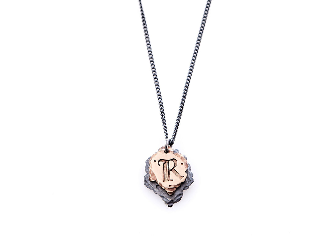 "Hand crafted, customizable Initial Necklace with 2 jagged-edged plates hanging from an oxidized sterling silver curbed chain. Top plate is hand forged rose gold with a custom engraving of the letter ""R"" in Old English lettering with 2 hand engraved dots on either side. Bottom plate is hand forged oxidized sterling silver and slightly larger than the rose gold plate. The top plate partially covers the bottom plate, and edges of cross- bones are visible on the bottom plate."