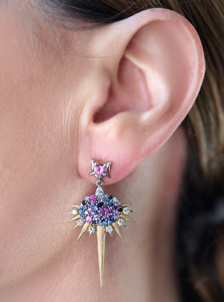 Closeup on an ear wearing the Harlin Jones mixed color sapphire drop earring. The stud fits snugly against the earlobe with the earring's drop extending down to mid- chin height.