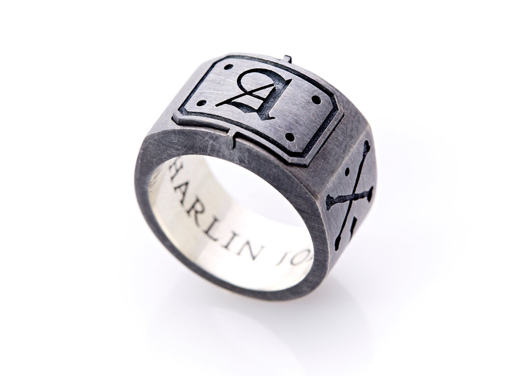 "Text: Side view of a bespoke jewelry design, the signet ring, balanced on its base. The A insignia is at the center of the head of the ring which is slightly thicker and less convex. Black engraved text on the interior polished sterling silver base of the band is visible which reads, ""Harlin Jones."""
