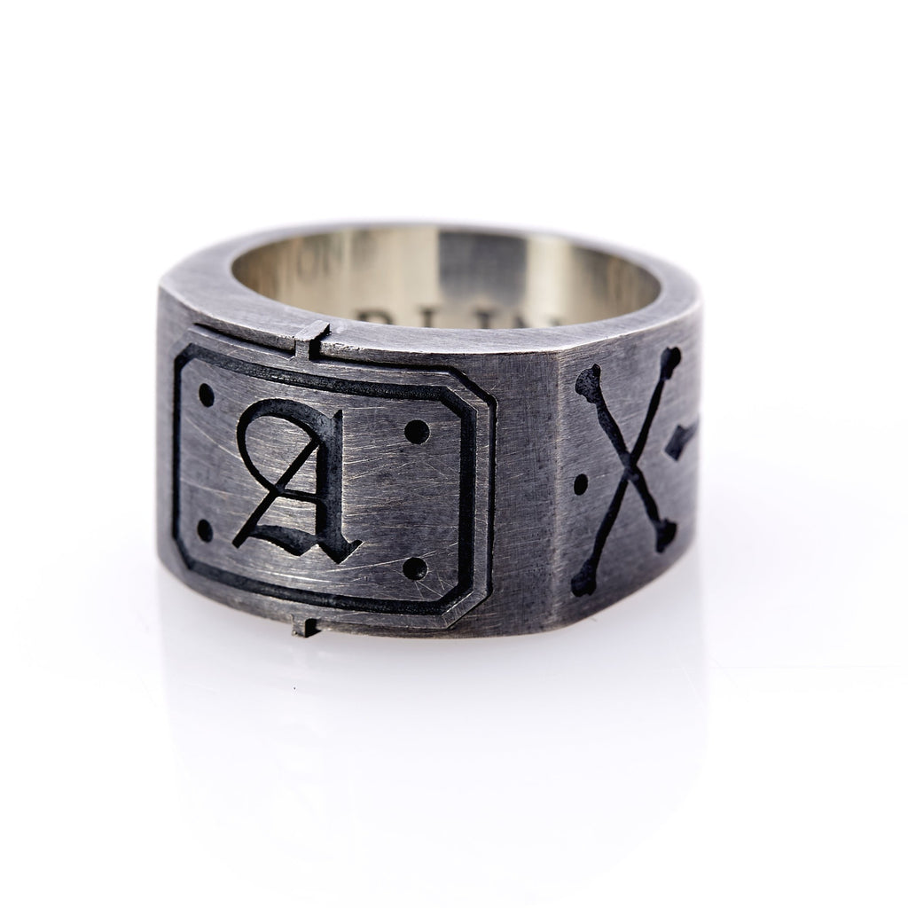 "Oxidized sterling silver men's signet ring with a thick flat band hand-crafted in New York. Semi-raised octagonal engraved top cap with a customizable insignia design of an engraved letter ""A"" in Old English Style lettering and 4 engraved dots at each corner. The initial on the ring is surrounded by a bold black engraved border that follows the inside edge of the rectangle. The rectangle's top and bottom edge is accented by a small lip in the center that wraps around the corner edge of the ring."