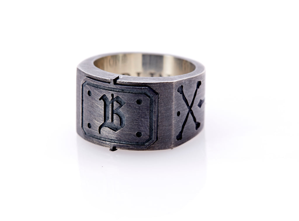 "Oxidized sterling silver men's signet ring with a thick flat band hand-crafted in New York. Semi-raised octagonal engraved top cap with a customizable insignia design of an engraved letter ""B"" in Old English Style lettering and 4 engraved dots at each corner. The initial on the ring is surrounded by a bold black engraved border that follows the inside edge of the rectangle. The rectangle's top and bottom edge is accented by a small lip in the center that wraps around the corner edge of the ring."