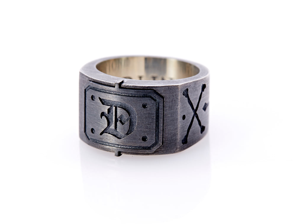 "Oxidized sterling silver men's signet ring with a thick flat band hand-crafted in New York. Semi-raised octagonal engraved top cap with a customizable insignia design of an engraved letter ""D"" in Old English Style lettering and 4 engraved dots at each corner. The initial on the ring is surrounded by a bold black engraved border that follows the inside edge of the rectangle. The rectangle's top and bottom edge is accented by a small lip in the center that wraps around the corner edge of the ring."