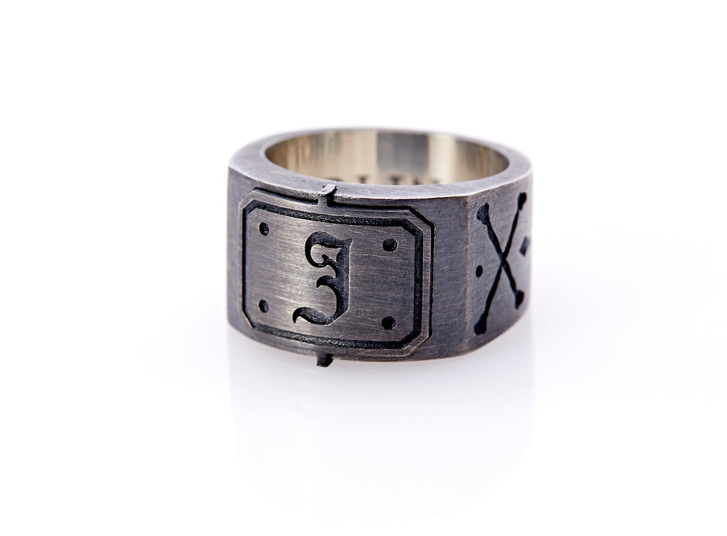 "Oxidized sterling silver men's signet ring with a thick flat band hand-crafted in New York. Semi-raised octagonal engraved top cap with a customizable insignia design of an engraved letter ""J"" in Old English Style lettering and 4 engraved dots at each corner. The initial on the ring is surrounded by a bold black engraved border that follows the inside edge of the rectangle. The rectangle's top and bottom edge is accented by a small lip in the center that wraps around the corner edge of the ring."