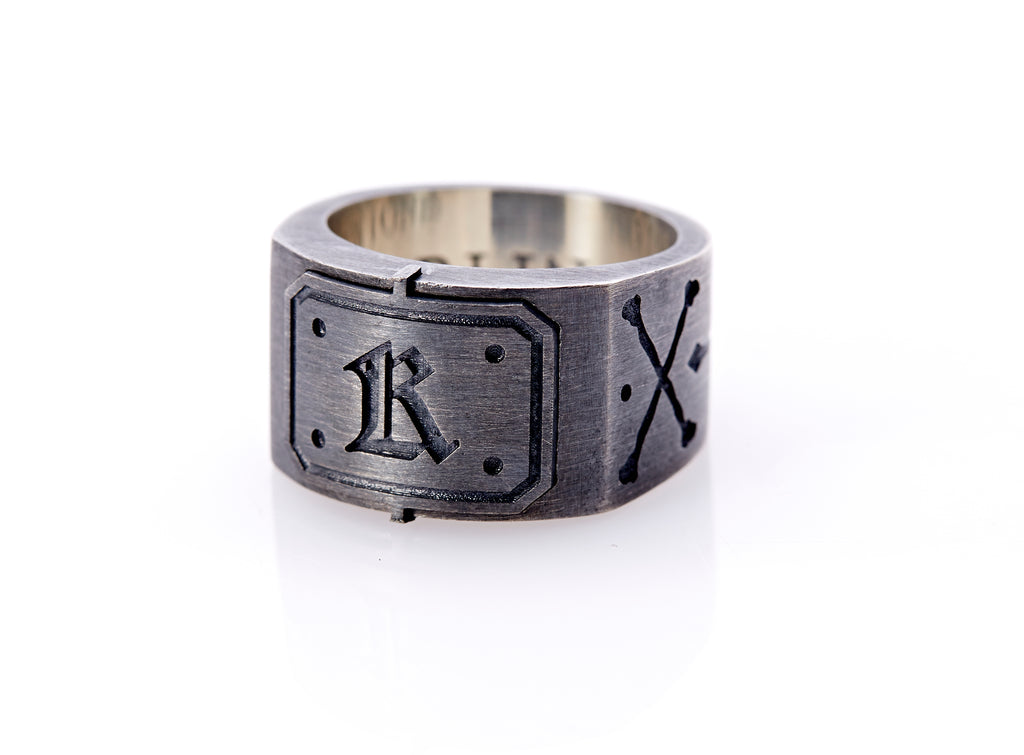 "Oxidized sterling silver men's signet ring with a thick flat band hand-crafted in New York. Semi-raised octagonal engraved top cap with a customizable insignia design of an engraved letter ""K"" in Old English Style lettering and 4 engraved dots at each corner. The initial on the ring is surrounded by a bold black engraved border that follows the inside edge of the rectangle. The rectangle's top and bottom edge is accented by a small lip in the center that wraps around the corner edge of the ring."