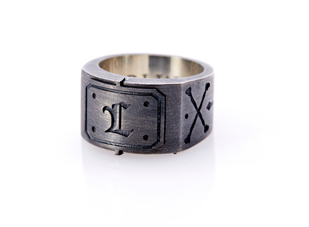 "Oxidized sterling silver men's signet ring with a thick flat band hand-crafted in New York. Semi-raised octagonal engraved top cap with a customizable insignia design of an engraved letter ""L"" in Old English Style lettering and 4 engraved dots at each corner. The initial on the ring is surrounded by a bold black engraved border that follows the inside edge of the rectangle. The rectangle's top and bottom edge is accented by a small lip in the center that wraps around the corner edge of the ring."
