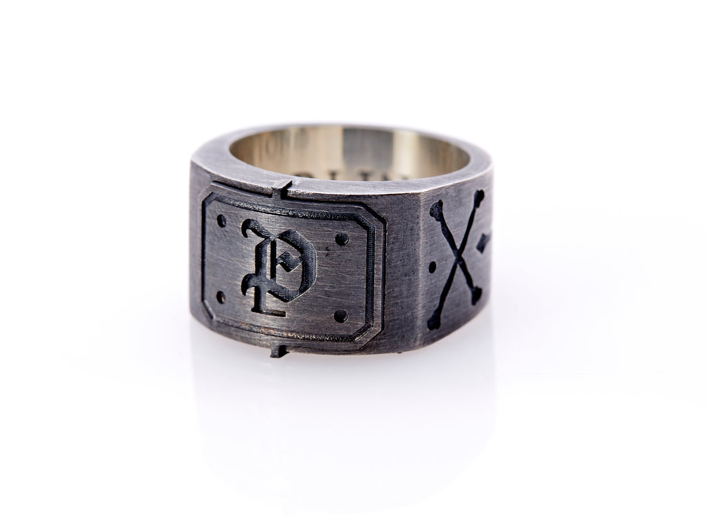 "Oxidized sterling silver men's signet ring with a thick flat band hand-crafted in New York. Semi-raised octagonal engraved top cap with a customizable insignia design of an engraved letter ""P"" in Old English Style lettering and 4 engraved dots at each corner. The initial on the ring is surrounded by a bold black engraved border that follows the inside edge of the rectangle. The rectangle's top and bottom edge is accented by a small lip in the center that wraps around the corner edge of the ring."