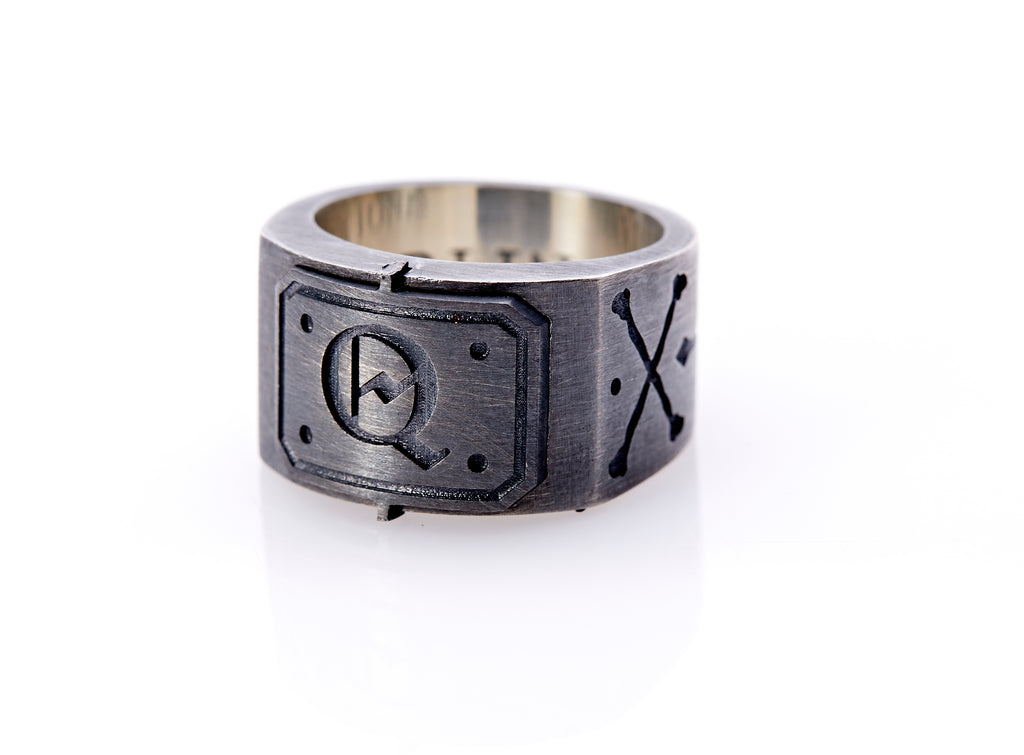 "Oxidized sterling silver men's signet ring with a thick flat band hand-crafted in New York. Semi-raised octagonal engraved top cap with a customizable insignia design of an engraved letter ""Q"" in Old English Style lettering and 4 engraved dots at each corner. The initial on the ring is surrounded by a bold black engraved border that follows the inside edge of the rectangle. The rectangle's top and bottom edge is accented by a small lip in the center that wraps around the corner edge of the ring."