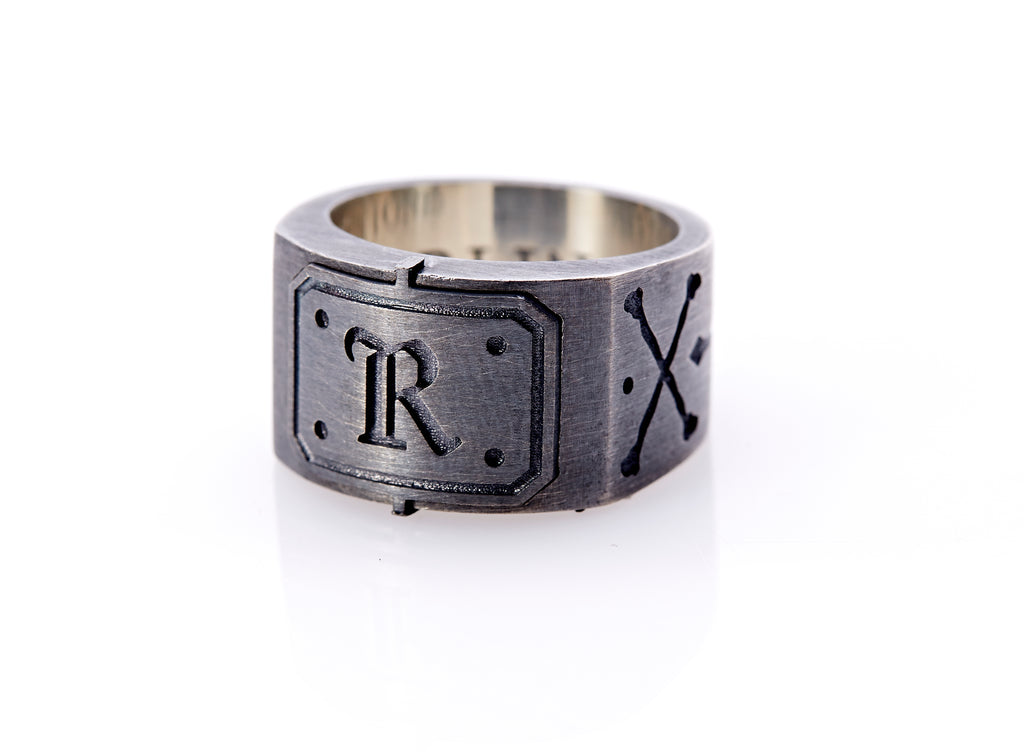 "Oxidized sterling silver men's signet ring with a thick flat band hand-crafted in New York. Semi-raised octagonal engraved top cap with a customizable insignia design of an engraved letter ""R"" in Old English Style lettering and 4 engraved dots at each corner. The initial on the ring is surrounded by a bold black engraved border that follows the inside edge of the rectangle. The rectangle's top and bottom edge is accented by a small lip in the center that wraps around the corner edge of the ring."