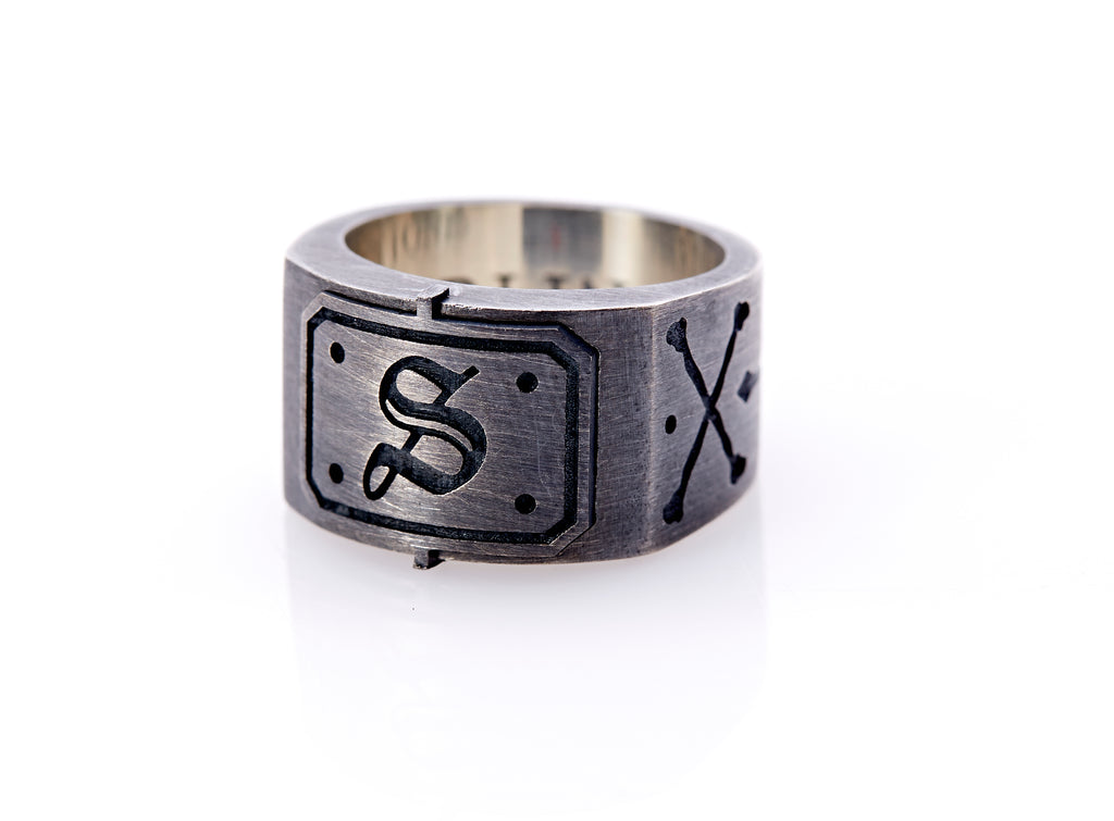 "Oxidized sterling silver men's signet ring with a thick flat band hand-crafted in New York. Semi-raised octagonal engraved top cap with a customizable insignia design of an engraved letter ""S"" in Old English Style lettering and 4 engraved dots at each corner. The initial on the ring is surrounded by a bold black engraved border that follows the inside edge of the rectangle. The rectangle's top and bottom edge is accented by a small lip in the center that wraps around the corner edge of the ring."