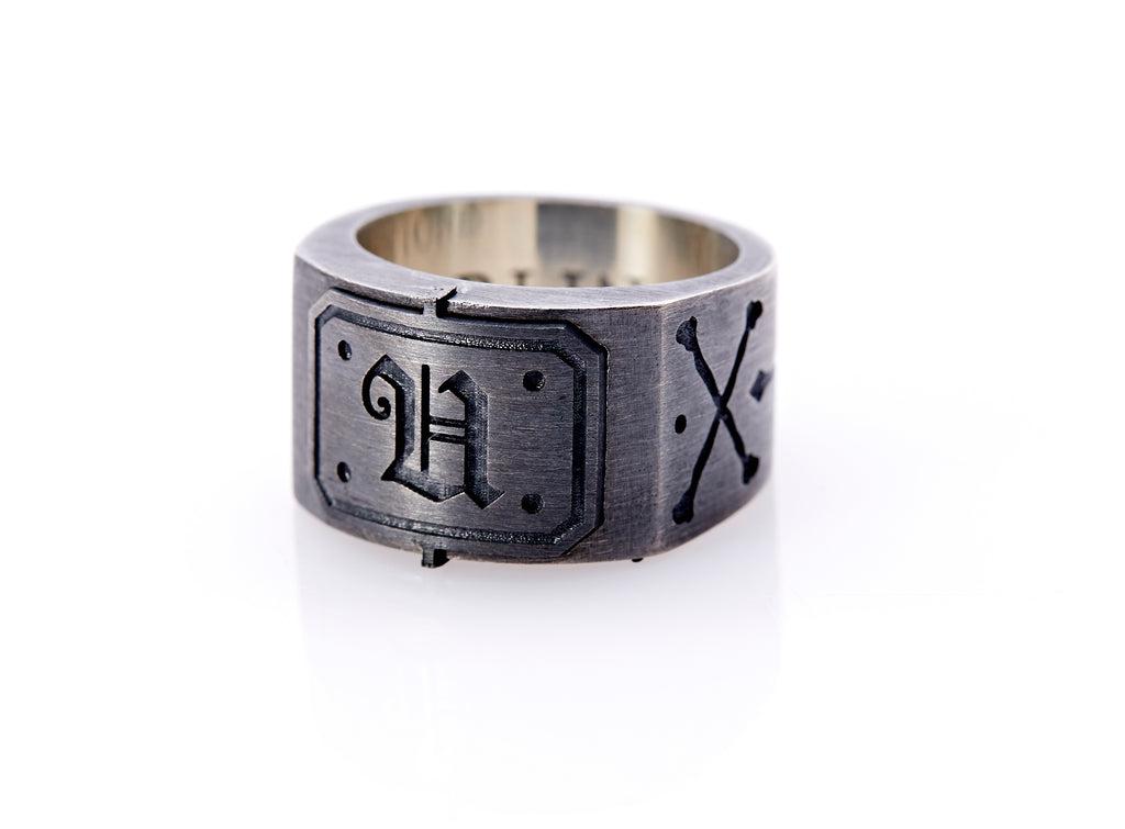 "Oxidized sterling silver men's signet ring with a thick flat band hand-crafted in New York. Semi-raised octagonal engraved top cap with a customizable insignia design of an engraved letter ""U"" in Old English Style lettering and 4 engraved dots at each corner. The initial on the ring is surrounded by a bold black engraved border that follows the inside edge of the rectangle. The rectangle's top and bottom edge is accented by a small lip in the center that wraps around the corner edge of the ring."