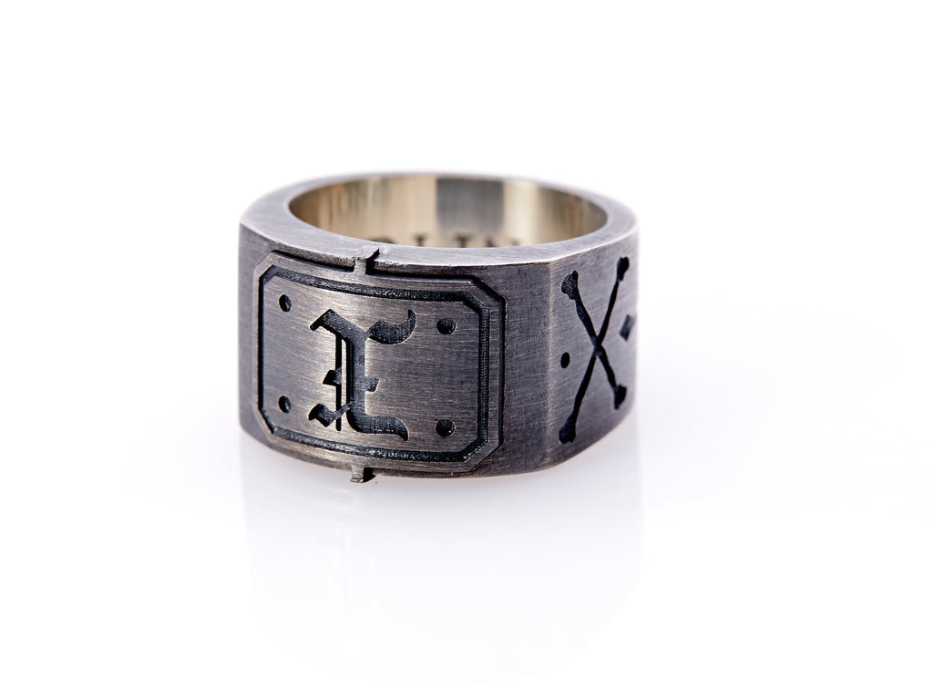 "Oxidized sterling silver men's signet ring with a thick flat band hand-crafted in New York. Semi-raised octagonal engraved top cap with a customizable insignia design of an engraved letter ""X"" in Old English Style lettering and 4 engraved dots at each corner. The initial on the ring is surrounded by a bold black engraved border that follows the inside edge of the rectangle. The rectangle's top and bottom edge is accented by a small lip in the center that wraps around the corner edge of the ring."