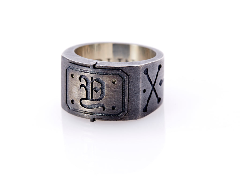 "Oxidized sterling silver men's signet ring with a thick flat band hand-crafted in New York. Semi-raised octagonal engraved top cap with a customizable insignia design of an engraved letter ""Y"" in Old English Style lettering and 4 engraved dots at each corner. The initial on the ring is surrounded by a bold black engraved border that follows the inside edge of the rectangle. The rectangle's top and bottom edge is accented by a small lip in the center that wraps around the corner edge of the ring."