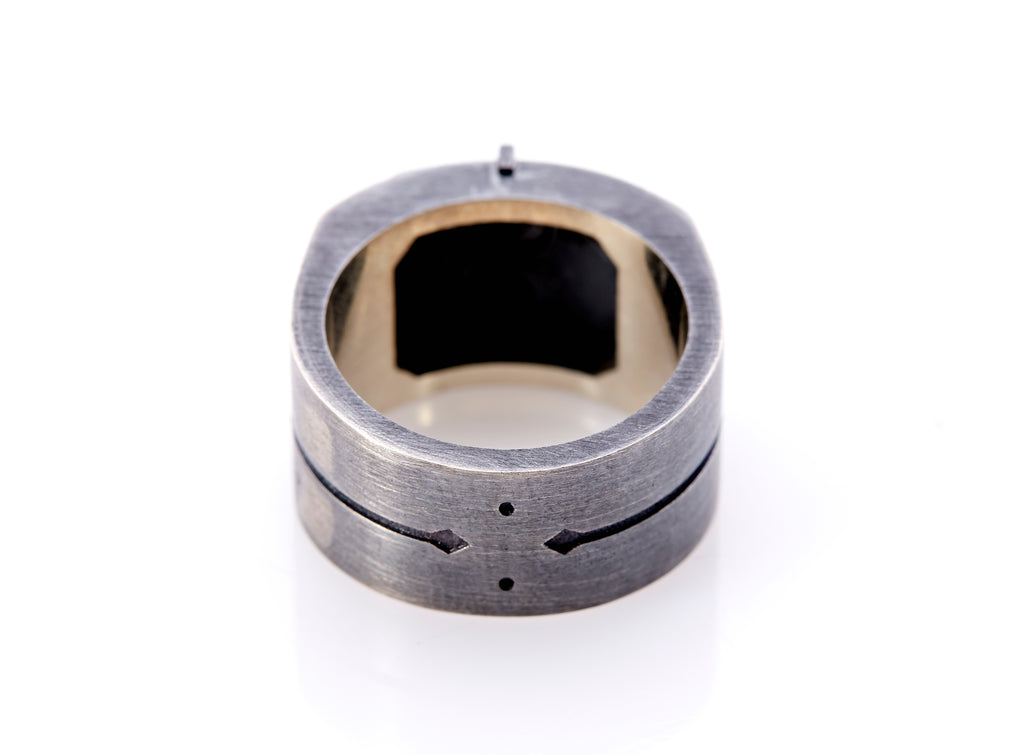 Base of signet ring with details of arrows and dots. The oxidized silver has a brushed finish. Inner band of the ring's top is visible which has an octagonal square for the ring's insignia.