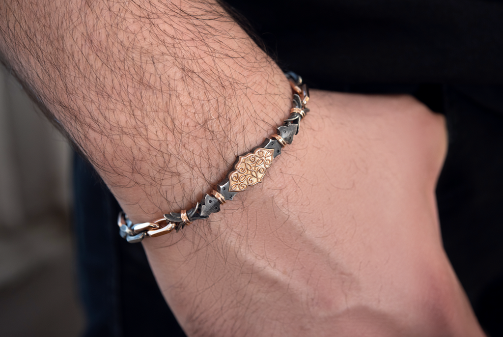 Closeup on man's wrist wearing the Harlin Jones oxidized sterling silver and rose gold bracelet. The filigree plate sits in the center of the wrist and is roughly the size of a Tic Tac. As the arm points downwards, the bracelet falls to where the wrist meets the hand. The bracelet is the width of a thick rubber band.