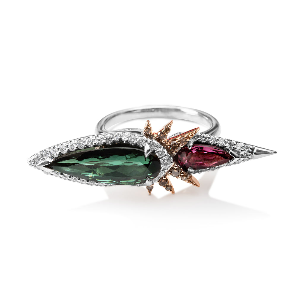 Bespoke tourmaline and diamond ring with thin, round white gold band. Pear- shaped green tourmaline gem surrounded by round diamonds. The pointed edge extends horizontally from the ring's center. A smaller pink tourmaline pear-shaped gem extends horizontally in the opposite direction, surrounded by round diamonds. The pink stone has a sharp white gold point at the end and is set below the green gem. 6 rose gold diamond spikes extend out from center to overlap the pink gem.