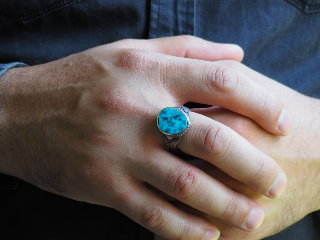 Closeup on man's hand wearing the Turquoise Cross-Bones Ring on his middle finger. The ring's band fits low around the base of the knuckle. The ring's stone extends from the base of the knuckle to halfway below the first joint, with the cross-bones on the side of the band visible.