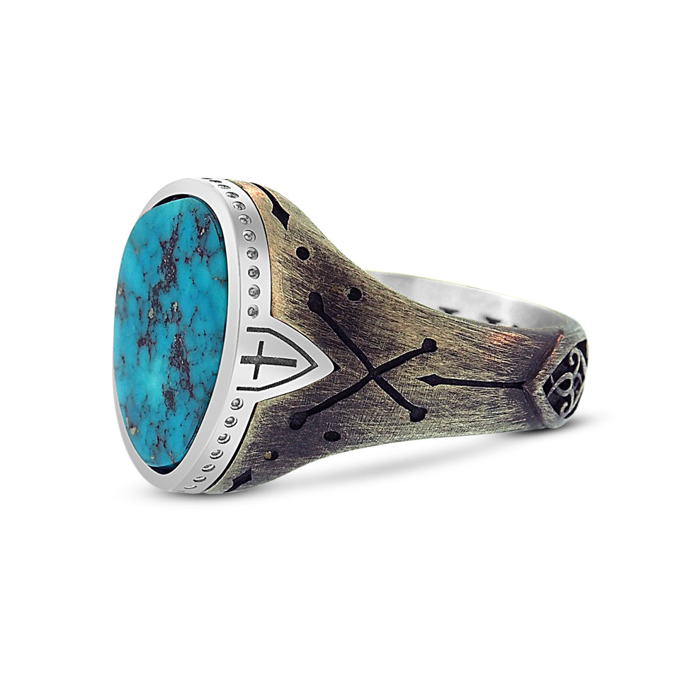 Partial side view of the men's turquoise ring shows the large stone setting tapering into a thin metal band. Polished sterling silver bezel setting sits like a cap on the ring with a continuous pattern of small circular engravings around the perimeter. There is an engraving of a cross within a shield on the bezel on either side of the stone that drops into the band. The sterling silver band has a custom engraving of cross-bones that sit just below the cross and shield.